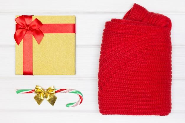 Coffret cadeau canne en bonbon plié pull rouge sur des planches de bois blanc concept de noël à plat