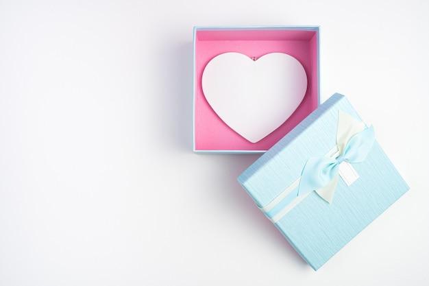 Coffret cadeau avec un cœur à l'intérieur sur fond clair.