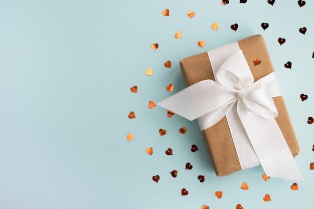 Coffret cadeau et coeurs dorés scintille sur fond bleu clair. concept de vacances