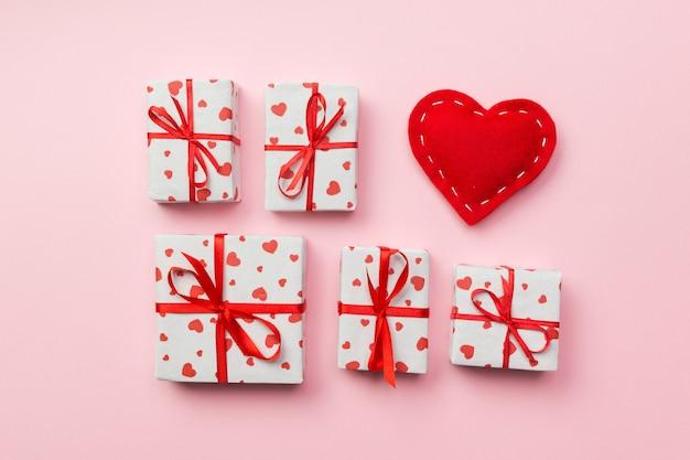 Coffret cadeau avec des coeurs rouges sur fond corail. vue de dessus avec espace de copie
