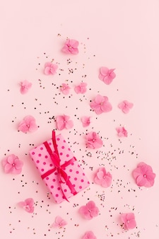 Coffret cadeau confettis paillettes d'or et fleurs sur l'espace de copie de vacances rose