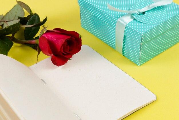Coffret cadeau à côté du bloc-notes et d'une fleur.