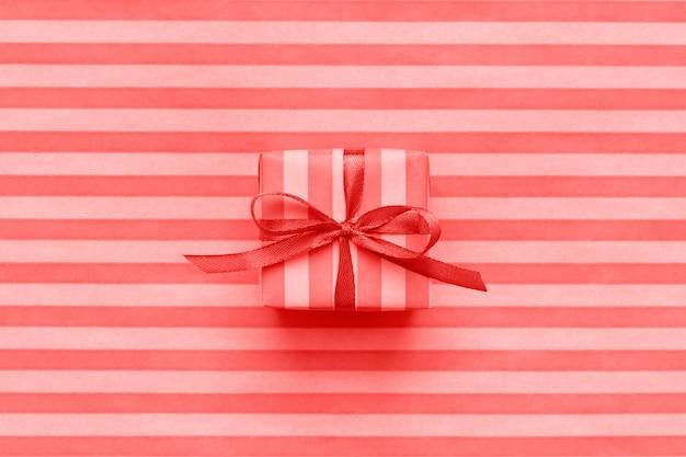 Coffret cadeau couleur corail vivant sur papier cadeau rayé.