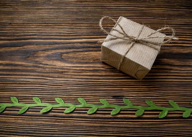 Coffret cadeau dans un emballage artisanal écologique sur une planche naturelle décorée d'un ruban vert avec des feuilles