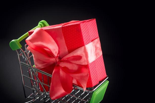 Coffret cadeau dans un emballage de fête avec noeud en satin dans le panier.