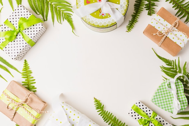 Coffret cadeau décoratif et feuilles brindille disposées sur fond blanc