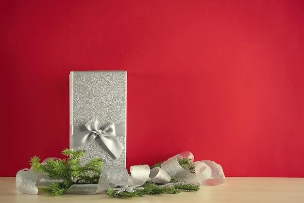 Coffret cadeau et décorations de noël sur table contre mur de couleur