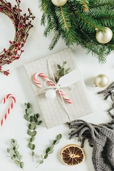 Coffret cadeau décoré de bonbons, eucalyptus, étiquette; cadres de guirlande faits de branches de sapin et de baies rouges. composition de vacances de noël. mise à plat, vue de dessus