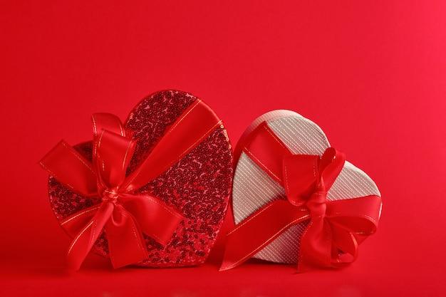 Coffret cadeau divers choix en forme de coeur avec un ruban rouge sur fond rouge. carte postale de concept de saint valentin. vue de dessus à plat avec espace de copie.