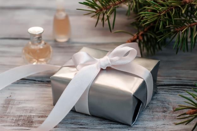 Coffret cadeau élégant de noël en papier argenté avec ruban rose et flacons de parfum