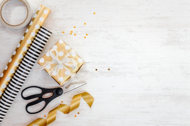 Coffret cadeau emballé dans du papier à pois doré et des matériaux d'emballage