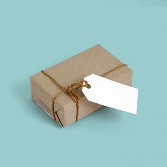 Coffret cadeau emballé dans du papier recyclé brun et une corde de sac noué avec une étiquette