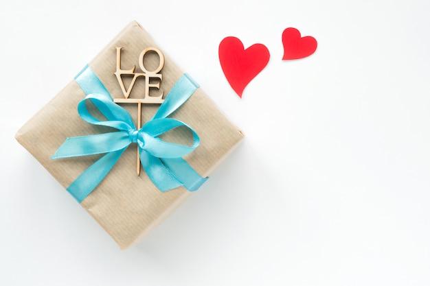 Coffret cadeau enveloppé dans du papier brun avec ruban bleu et coeurs rouges