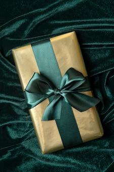 Coffret cadeau enveloppé dans du papier doré avec ruban satin vert marée