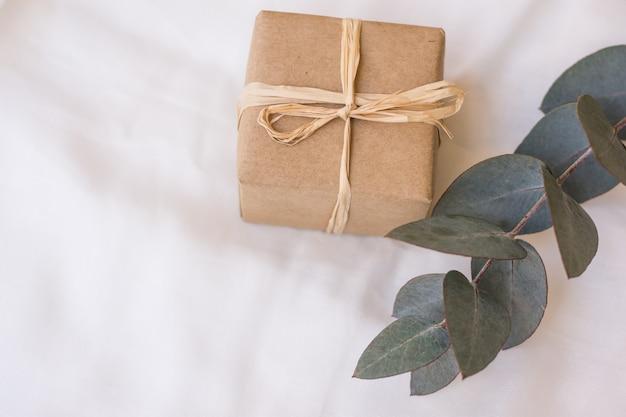 Coffret cadeau enveloppé dans du papier kraft marron avec une branche d'eucalyptus sur un tissu en lin blanc