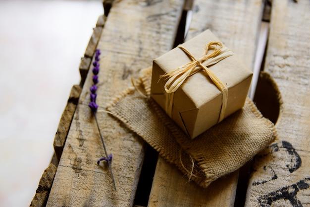 Coffret cadeau enveloppé dans du papier kraft sur toile de jute