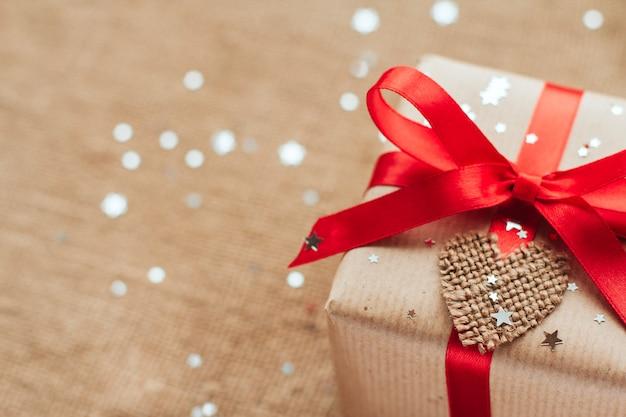 Coffret cadeau enveloppé dans du papier marron avec un noeud rouge, saupoudré de paillettes argentées en forme d'étoile copie espace, cadeau de noël