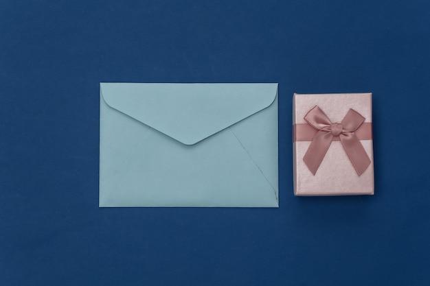 Coffret cadeau et enveloppe sur fond bleu classique. couleur 2020. vue de dessus