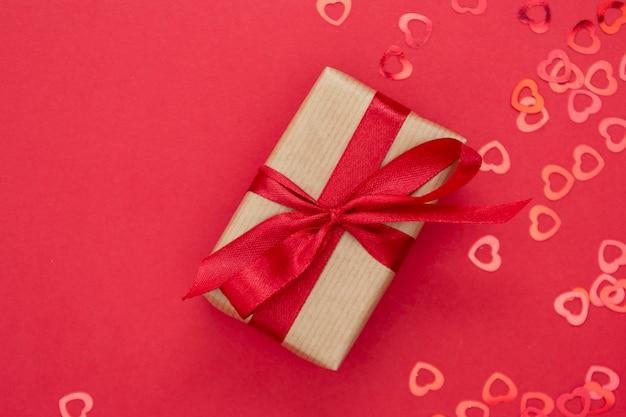 Coffret cadeau enveloppé de papier kraft et arc rouge isolé sur fond rouge. mise à plat abstraite.