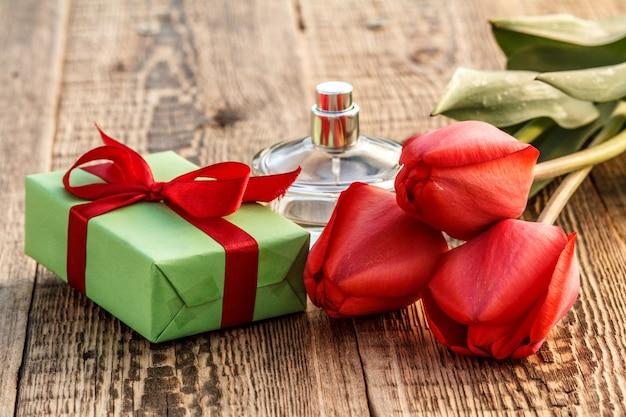 Coffret cadeau enveloppé d'un ruban rouge et d'une bouteille de parfum sur des planches en bois avec des tulipes rouges.