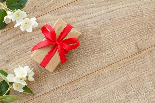 Coffret cadeau enveloppé de ruban rouge sur des planches en bois décorées de fleurs de jasmin. vue de dessus avec espace de copie.