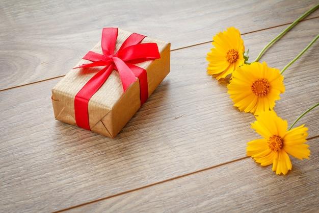 Coffret cadeau enveloppé de ruban rouge sur des planches en bois décorées de fleurs jaunes. vue de dessus.