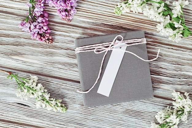 Coffret cadeau avec étiquette papier décorée de fleurs lilas sur une surface en bois ancien. mise à plat. copiez l'espace.