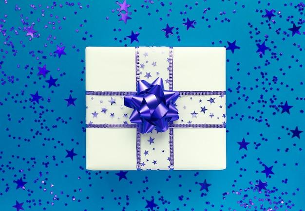 Coffret cadeau et étoiles sur fond bleu. mise à plat monochrome.
