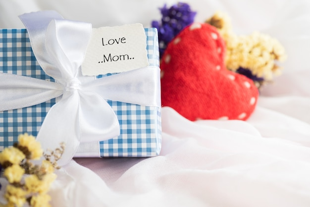Coffret cadeau avec fleur pourpre, étiquette en papier avec love mom et coeur rouge