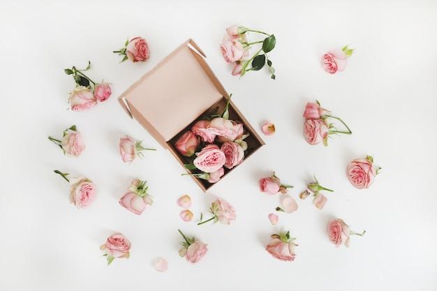 Coffret cadeau avec des fleurs roses roses sur fond blanc vue de dessus