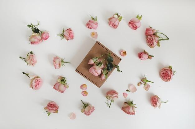Coffret cadeau avec des fleurs roses roses sur fond blanc