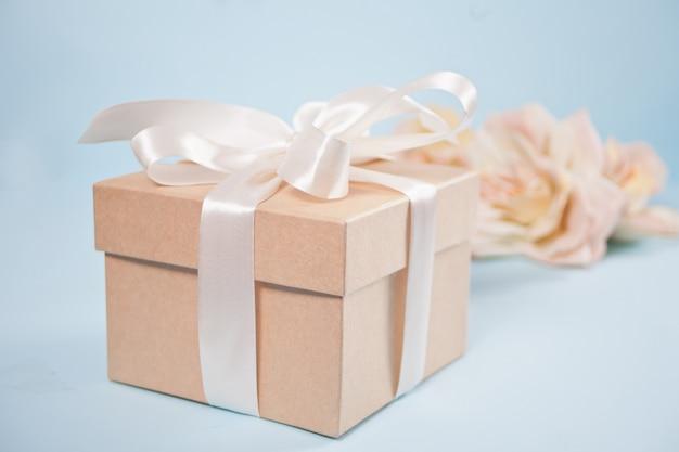 Coffret cadeau avec des fleurs roses roses sur le fond.