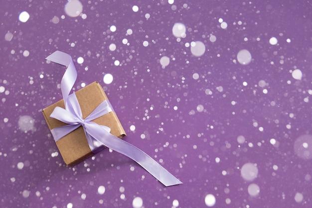 Coffret cadeau sur fond texturé violet.