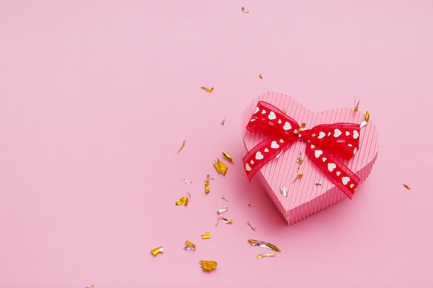 Coffret cadeau en forme de coeur sur fond rose avec des particules de paillettes festives volantes