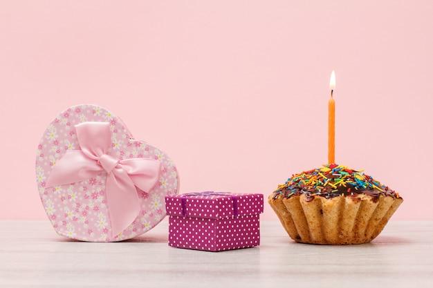 Coffret cadeau en forme de coeur et petit, savoureux muffin d'anniversaire avec glaçage au chocolat et caramel, décoré d'une bougie festive brûlante sur fond bois et rose. concept de joyeux anniversaire.