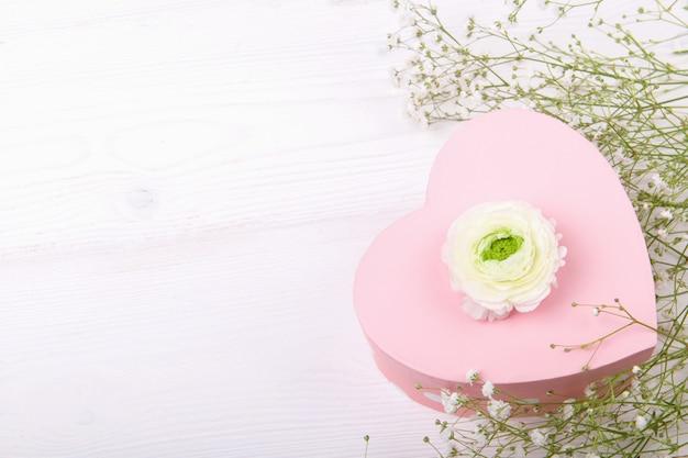 Coffret cadeau en forme de coeur rose sur fond blanc avec de petites fleurs blanches, célébration de la saint-valentin