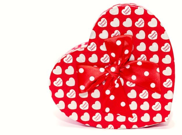 Coffret cadeau en forme de coeur rouge isolé sur fond blanc.