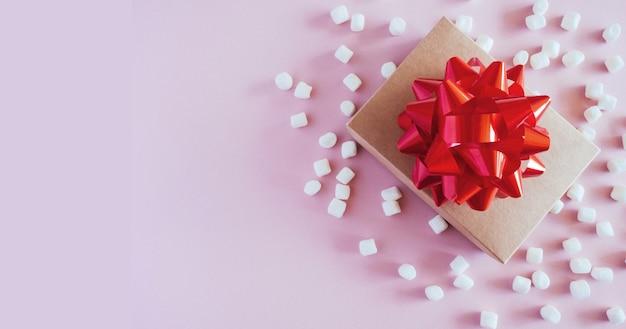Coffret cadeau avec gros noeud rouge sur fond rose. cadeau d'anniversaire, nouvel an, coffret cadeau de noël, saint valentin.