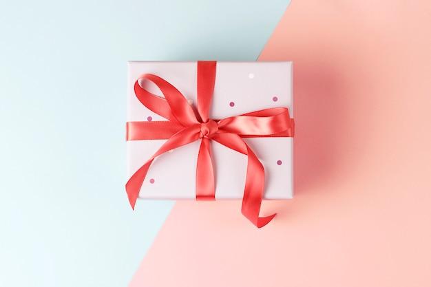 Coffret cadeau sur gros plan fond rose et bleu, vue de dessus