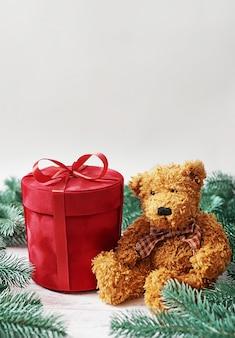 Coffret cadeau joyeux noël et carte de voeux ours en peluche. cadeaux, branches de sapin. cadeau de nouvel an de luxe rouge. célébration de noël.