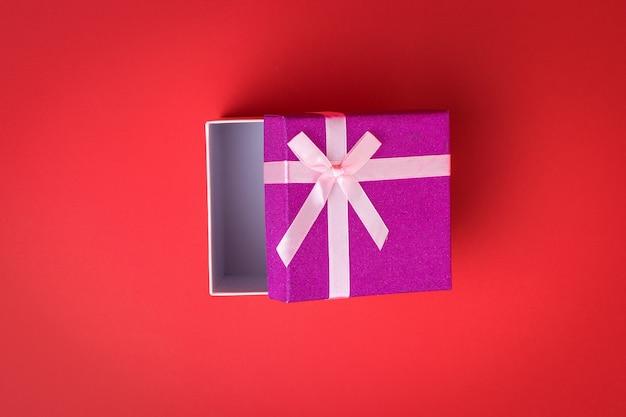 Coffret cadeau légèrement ouvert sur fond rouge. un cadeau de vacances.