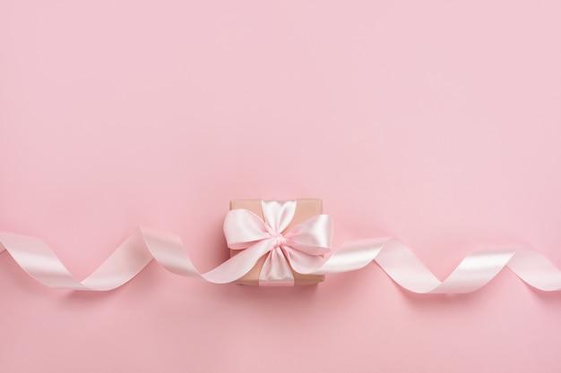 Coffret cadeau avec long ruban sur fond rose pastel. cadeau pour la saint valentin
