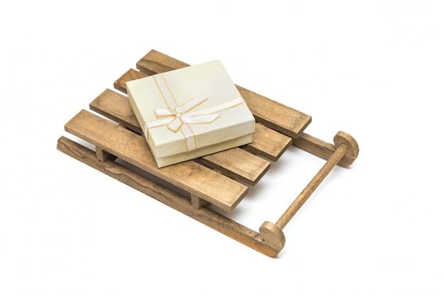 Coffret cadeau lumière sur traîneau en bois sur fond blanc. isolé sur blanc