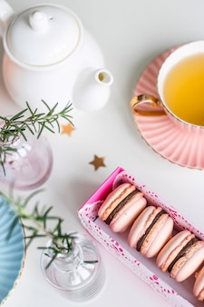 Coffret cadeau avec macarons roses parmi des coupes vintage de thé vert, des étoiles et des petits vases