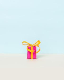 Coffret cadeau magenta avec ruban jaune sur fond pastel.