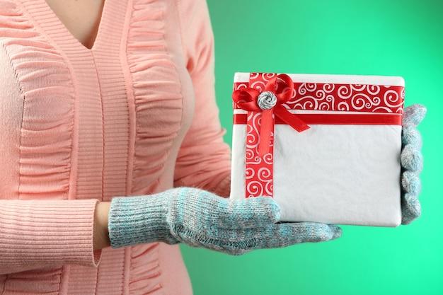 Coffret cadeau en main féminine sur une surface de couleur