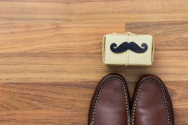 Coffret cadeau, moustache en papier, chaussures sur fond en bois avec espace de copie. joyeuse fête des pères.