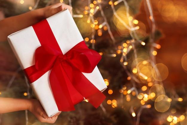 Coffret cadeau de noël avec un arc rouge dans les mains des enfants sur un fond d'éclairage