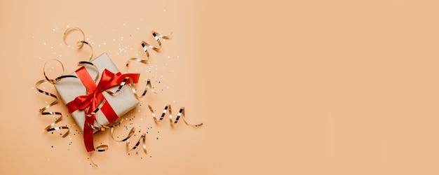 Coffret cadeau de noël avec un arc de ruban rouge et des décorations dorées sur fond pastel.
