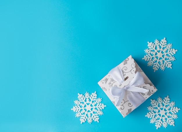Coffret cadeau de noël blanc et décor de noël blanc sur fond bleu. vue de dessus,